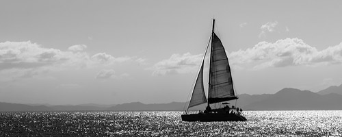 A sailboat sails towards the horizon.