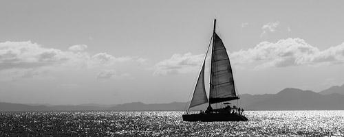 A sailboat sails towards the horizon.