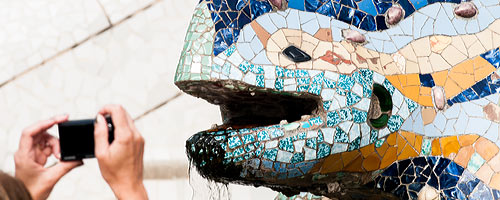 An image of a visitor taking a picture of the Gaudi lizzard at park Guell.