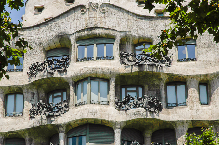 A close up look at a section of the Pedrera`s facade, iron balconies and windows.